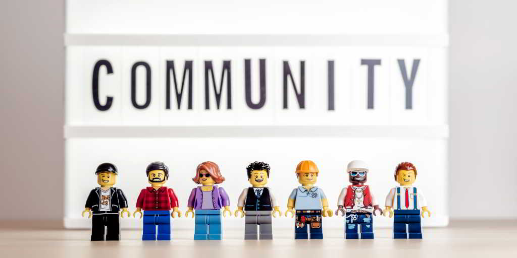 A variety of lego people standing under a sign reading community