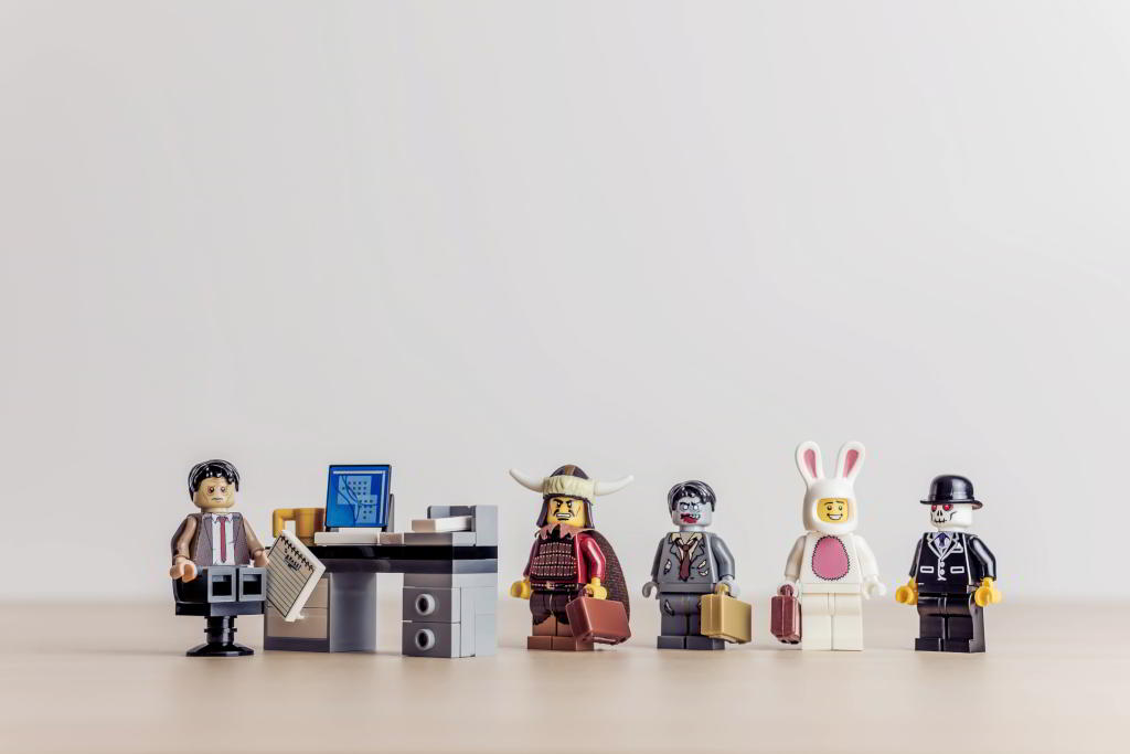 Lego office manager feeling very frightened and confused, as he is surrounded by a zombie, a Mongolian warrior, a skeleton, and a guy in a bunny suit.