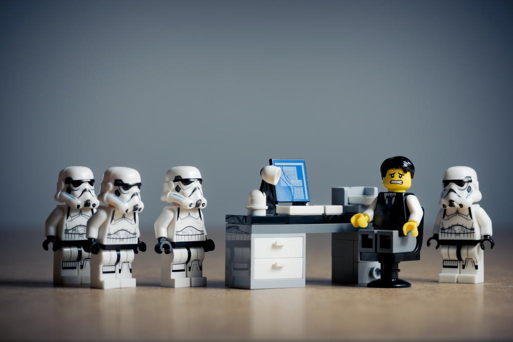 Lego business manager feeling very stressed out, surrounded by Star Wars Stormtroopers.