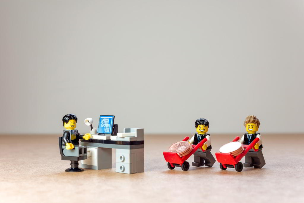Two Lego office workers delivering handcarts full of money to their manager.